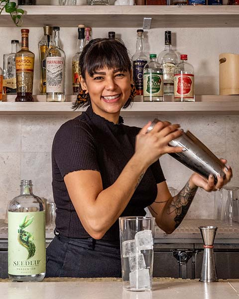 An adorable bartender laughing and smiling while shaking a cocktail photographed for the non-alcoholic spirit Seedlip.