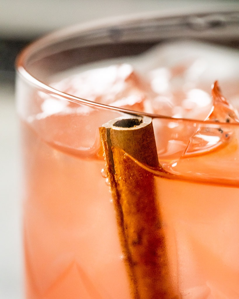 Cinnamon resting in a cocktail to infuse it with flavor